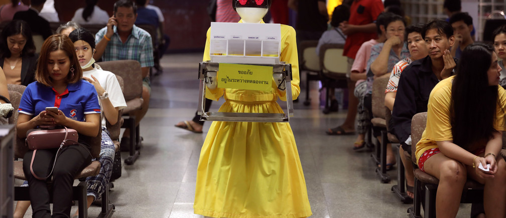 A robot wearing a nurse costume carries medical documents at Mongkutwattana General Hospital in Bangkok, Thailand, February 6, 2019. REUTERS/Athit Perawongmetha - RC1EA4F20BC0
