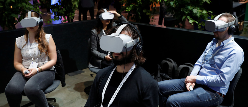 Attendees demo Oculus Go virtual reality headsets during Facebook Inc's F8 developers conference in San Jose, California, U.S., April 30, 2019