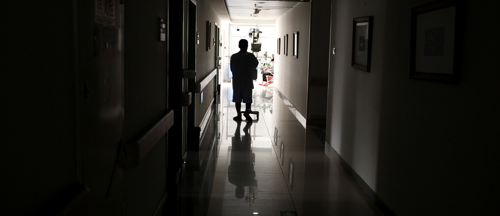 A cancer patient pushes his drip stand as he walks down the hallway of a hospital in Beijing, China July 12, 2011. REUTERS/David Gray/File Photo - S1AETORWYLAA
