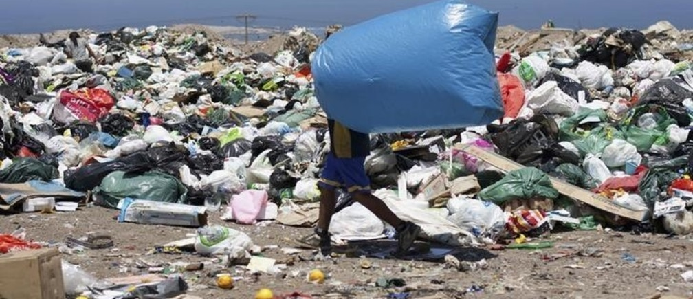 "A garbage collector carries a bag as he looks for recyclable waste at the ""La Chimba"", a 30.78 hectares garbage dump site in Antofagasta city, some 1317 km (818 miles) north of Santiago January 18, 2012. Some 150 people in extreme poverty live and work in the dump to search metals, plastics, cardboard and papers to sell, collecting near 160 kg of recyclables per person in a day. La Chimba, one of the largest dumps in Chile which receives around 130,000 tons of waste per year, will be shut down after more than 40 years and will be replaced with a recycling plant, according to local media. Picture taken January 18, 2012. REUTERS/Cristobal Saavedra (CHILE - Tags: SOCIETY ENVIRONMENT BUSINESS EMPLOYMENT)"