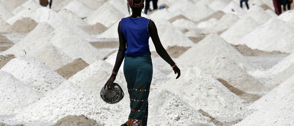 A woman walks across salt flats being cultivated for the white crystals near the village of Ngaye-Ngaye, 10 kilometers (six miles) south of Senegal's northern town of Saint Louis, April 9, 2007. Some 3,000 people, mostly women, spend long hours under the blinding sun scraping up salt with sticks and their hands, earning the equivalent of a dollar or two per day. REUTERS/Finbarr O'Reilly (SENEGAL) - RTR1OH5A