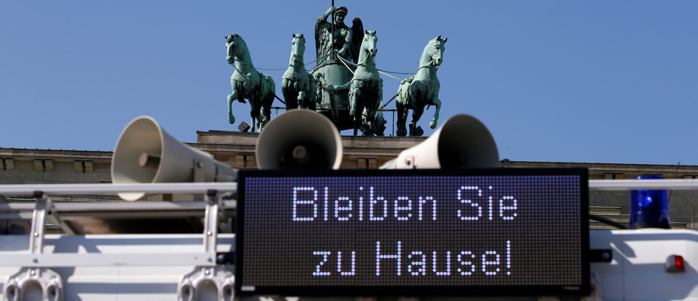 "A sign reading ""Stay at home!"" is attached to a police car in front of Brandenburg Gate, during the coronavirus disease (COVID-19) outbreak in Berlin, Germany April 5, 2020. REUTERS/Michele Tantussi - RC2AYF9NJZZP"
