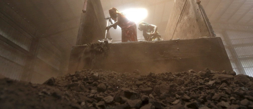 Workers unload coal from a supply truck at a yard on the outskirts of the western Indian city of Ahmedabad April 15, 2015. Fewer power cuts are likely in India this summer after a surge in output at Coal India helped generators amass record stocks, a turnaround for Narendra Modi who had to battle a power crisis within months of becoming prime minister last May. Fast-track mine approvals, tighter production oversight and more flexibility in coal sales have helped power station stocks recover from a six-year low hit in October, vindicating Modi's pitch to voters as the state leader who brought round-the-clock power to industrial Gujarat.