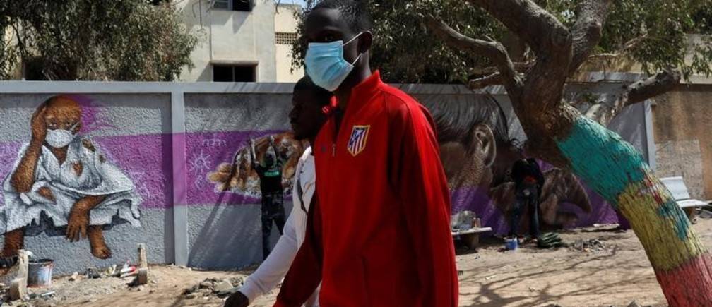 A man, wearing a face mask, walks past graffiti artists from RBS crew as they work on their mural to encourage people to protect themselves amid the outbreak of the coronavirus disease (COVID-19), in Dakar, Senegal March 25, 2020. Picture taken March 25, 2020. REUTERS/Zohra Bensemra - RC2BSF9YRFOB