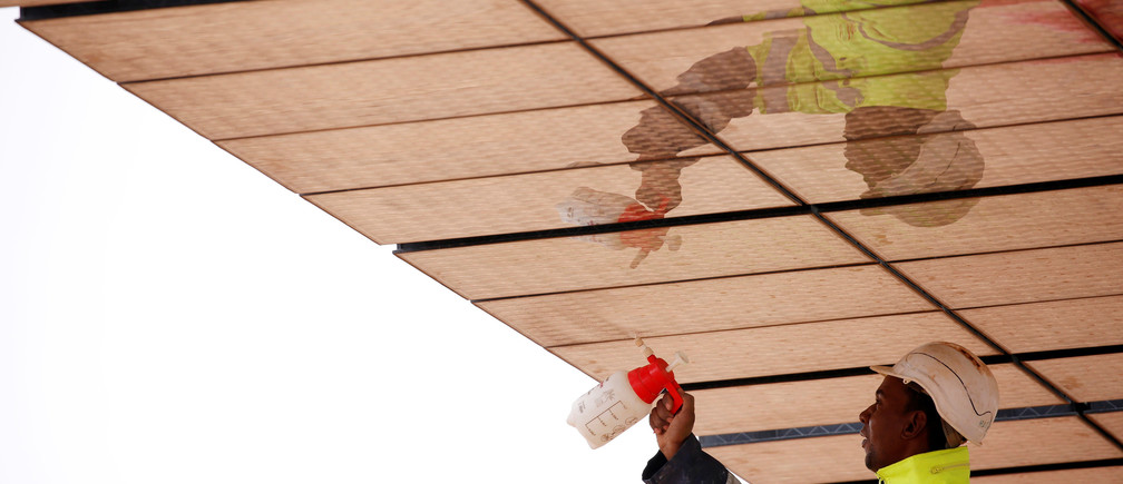 Workers clean solar panels at Noor III near the city of Ouarzazate, Morocco, November 4, 2016. Picture taken November 4, 2016. REUTERS/Youssef Boudlal - S1AEULCGPCAA
