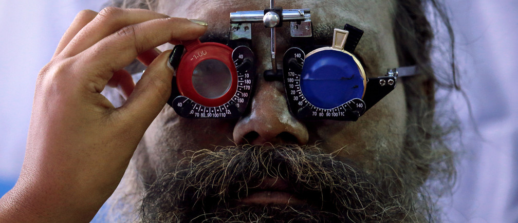 """A Sadhu or a Hindu holy man gets his eyes tested at a free eye-care camp at a makeshift shelter before heading for an annual trip to Sagar Island for the one-day festival of """"Makar Sankranti"""", in Kolkata, India, January 10, 2019"""