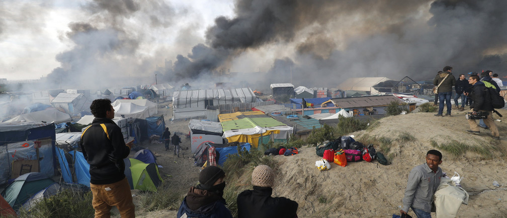 """Smoke rises the sky as migrants and journalists look at burning makeshift shelters and tents in the """"Jungle"""" on the third day of their evacuation and transfer to reception centers in France, as part of the dismantlement of the camp in Calais, France, October 26, 2016.          REUTERS/Philippe Wojazer TPX IMAGES OF THE DAY - LR1ECAQ0UA87V"""