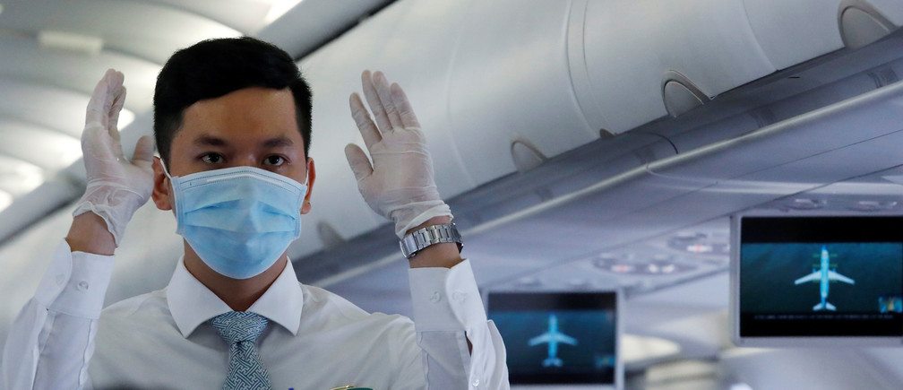 An attendant wearing a protective mask guides the flight safety procedures before take off of a Vietnam Airlines flight, following an outbreak of the novel coronavirus, at Danang airport in Danang city, Vietnam February 23, 2020. REUTERS/Kham - RC2C6F9UYSV4