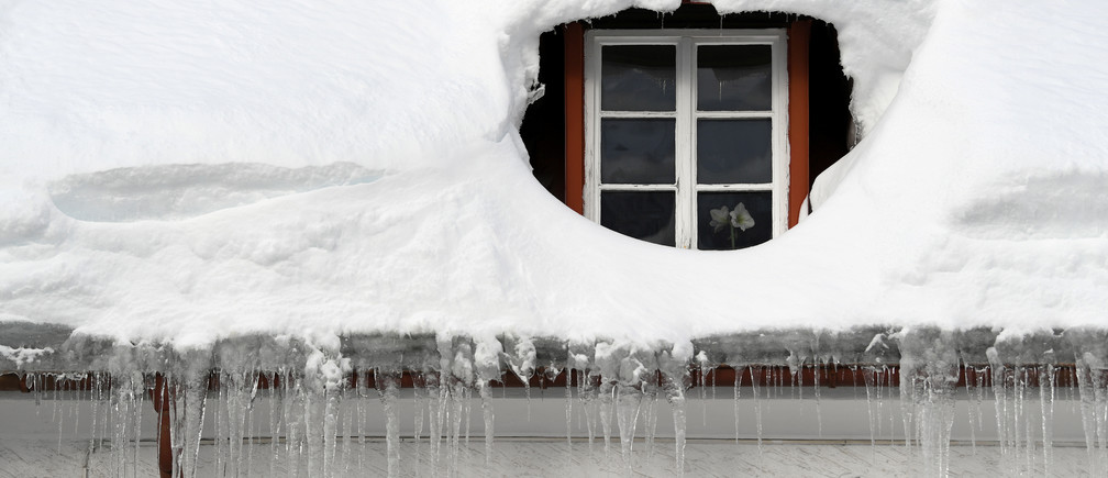 Icicles hang from a rain gutter on a house that is covered with snow in Oberjoch, Germany, January 15, 2019. REUTERS/Andreas Gebert - RC17CCC15F40
