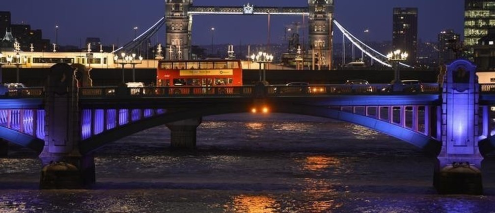 A London bus crosses the River Thames on London Bridge during the evening rush hour with Tower Bridge seen behind in London December 18, 2013.  REUTERS/Toby Melville (BRITAIN - Tags: SOCIETY CITYSCAPE)