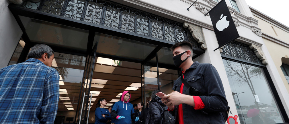 A person wears a face mask outside an Apple Store closed during the global outbreak of coronavirus (COVID-19) in Pasadena, California, U.S., March 14, 2020. REUTERS/Mario Anzuoni - RC2YJF9TQCB4