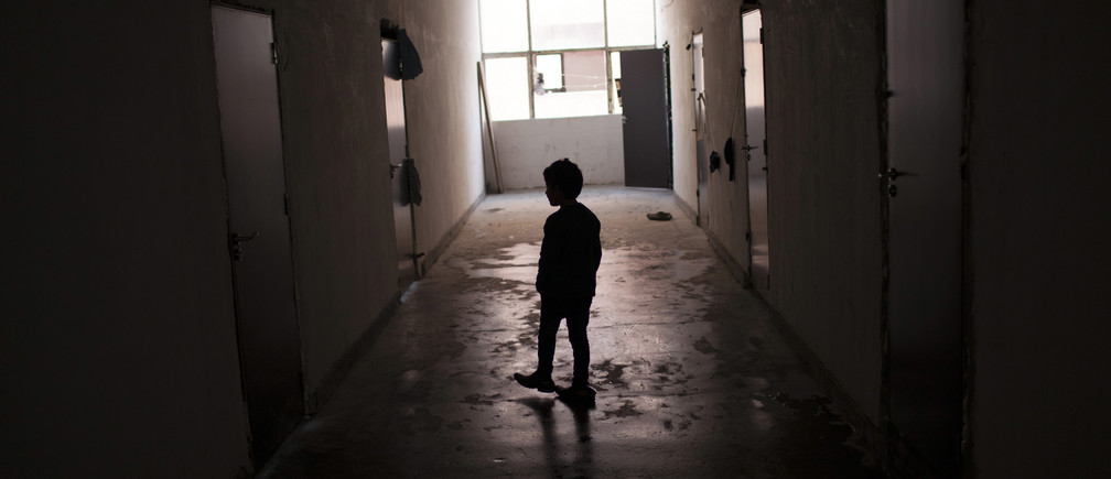 A Syrian boy walks along a corridor inside a refugee camp in Harmanli, 280 km (173 miles) east of Sofia, December 9, 2013. According to UNHCR, Bulgaria is currently hosting some 8,800 asylum seekers and refugees, around two-thirds of them being Syrians. Bulgaria, the European Union's poorest country, on average receives only around 1,000 asylum seekers and refugees a year. REUTERS/Pierre Marsaut (BULGARIA - Tags: SOCIETY IMMIGRATION POLITICS)