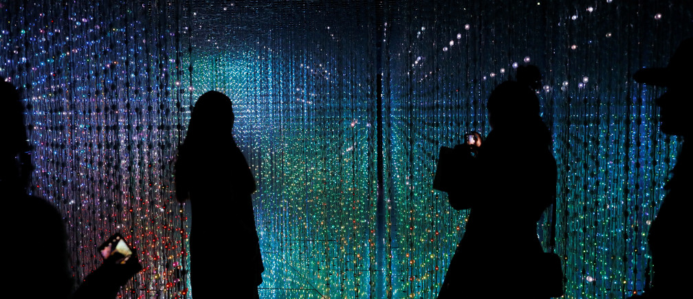 """Visitors look at a digital installation which is a part of """"Dance! Art Exhibition, Learn & Play!"""" by Japanese group teamLab in Taipei, Taiwan January 16, 2017. REUTERS/Tyrone Siu - RTSVOOT"""