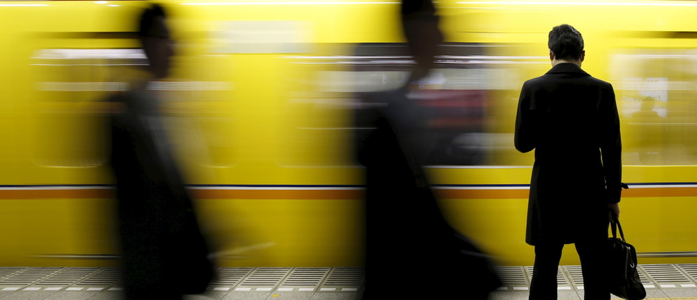 A man looks at his mobile phone as he waits for a subway at a station at a business district in Tokyo, Japan, February 19, 2016. Confidence at Japanese manufacturers remained largely subdued in February and the mood was seen deteriorating over the coming three months, a Reuters poll showed, highlighting concerns about slowing global growth and turbulent markets. REUTERS/Yuya Shino      TPX IMAGES OF THE DAY      - GF10000314709