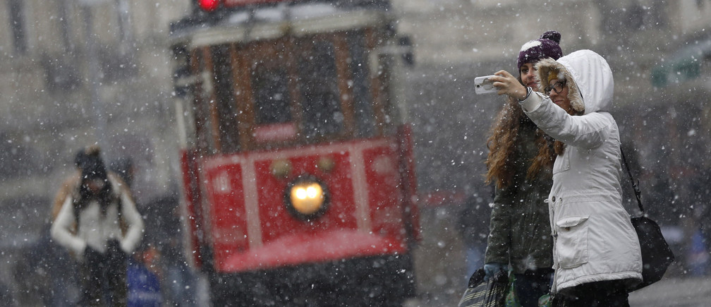 "Pedestrians, with a vintage tram in the background, take a ""selfie"" as snow falls at the main shopping street of Istiklal in central Istanbul January 6, 2015. REUTERS/Murad Sezer (TURKEY  - Tags: ENVIRONMENT SOCIETY) - GM1EB1702Y101"