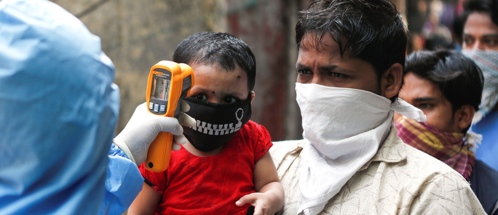 A doctor scans residents from Dharavi in Mumbai, India, one of Asia's largest informal settlements, with an infrared thermometer.