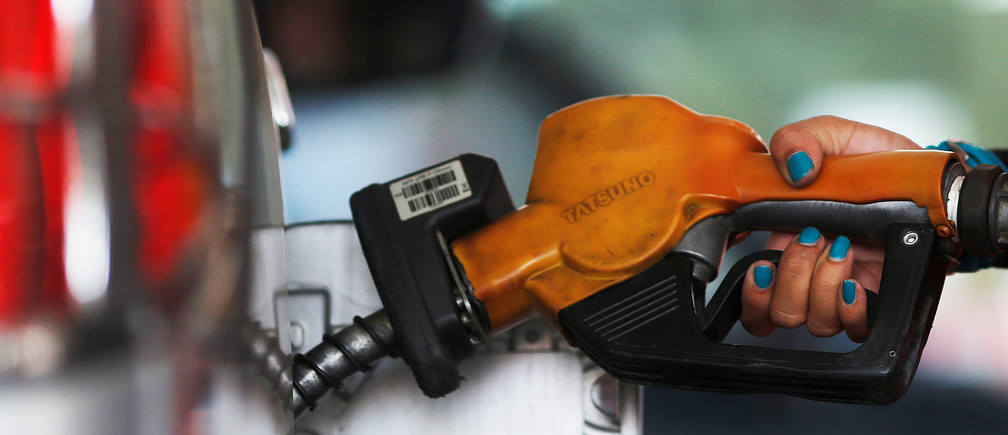 A worker at state-owned Pertamina, the country's main retailer of subsidised fuel, fills a vehicle at a petrol station in Jakarta November 17, 2014.  REUTERS/Beawiharta/File Photo - S1BEUDMCCLAA