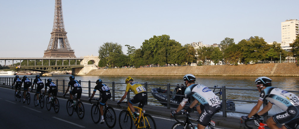 The pack of riders including Team Sky rider and leader's yellow jersey holder Christopher Froome of Britain cycle on the banks of the Seine river past the Eiffel Tower during the 133.5km final stage of the centenary Tour de France cycling race from Versailles to Paris Champs Elysees, July 21, 2013.   REUTERS/Eric Gaillard (FRANCE  - Tags: SPORT CYCLING)   - LR2E97L1G3XY7