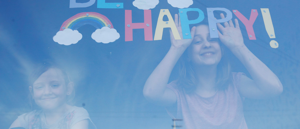 Sophie and Emily Ward pose for a photograph with their hand-drawn picture of rainbows and a message on their window in St Helens, as the spread of coronavirus disease (COVID-19) continues. St Helens, Britain, March 25, 2020. REUTERS/Phil Noble     TPX IMAGES OF THE DAY - RC20RF95EWP6