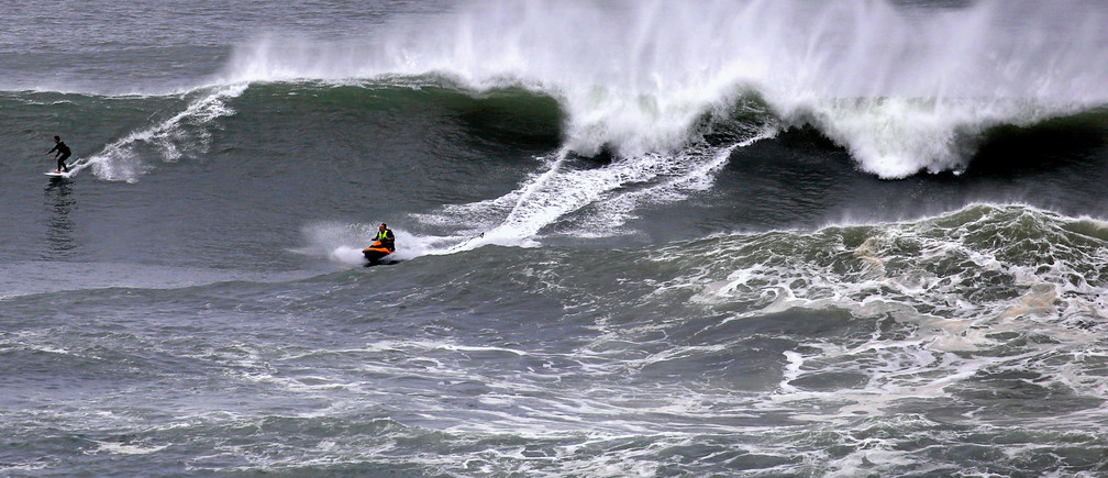 A surfer rides a large wave after being pulled onto it by a jet ski near Long Reef beach in Sydney, Australia, June 6, 2016.      REUTERS/David Gray - S1AETIHAHBAA