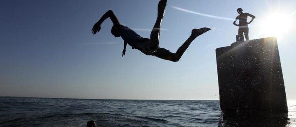 A boy jumps into the Mediterranean Sea, off the coast of Benghazi July 13, 2011. REUTERS/Esam Al-Fetori (LIBYA - Tags: ENVIRONMENT SOCIETY)