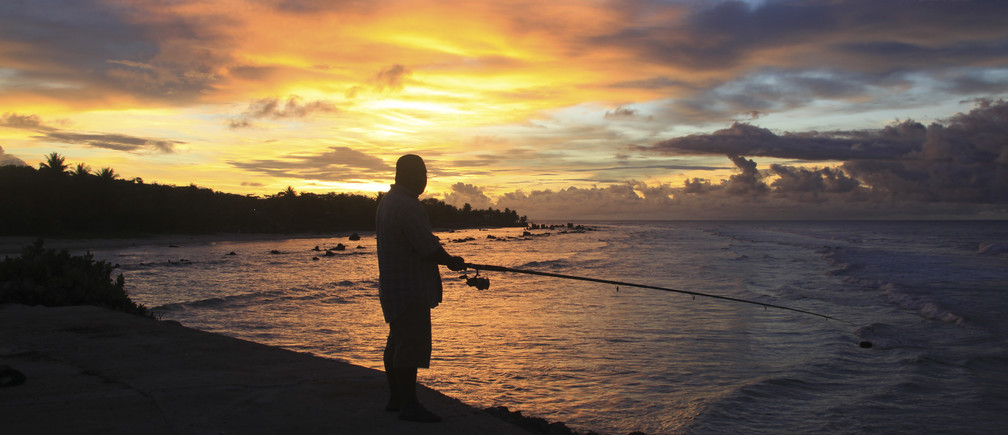 A fisherman is pictured at sunset at the northern end of the airport runway on the small nation island of Nauru, April 15, 2010. Australia has flooded Nauru with money since 2012, when the island became a key plank in its controversial policy of dealing with asylum seekers. Nauru hosts a detention centre able to hold 1,500 men, women and children from the Middle East, Africa and Asia who have been sent there after trying to get to Australia in rickety boats, usually from Indonesia.  Picture taken April 15, 2010. To match Insight AUSTRALIA-NAURU/     REUTERS/Rod Henshaw   (NAURU - Tags: POLITICS ENVIRONMENT SOCIETY IMMIGRATION) - RTX192VF