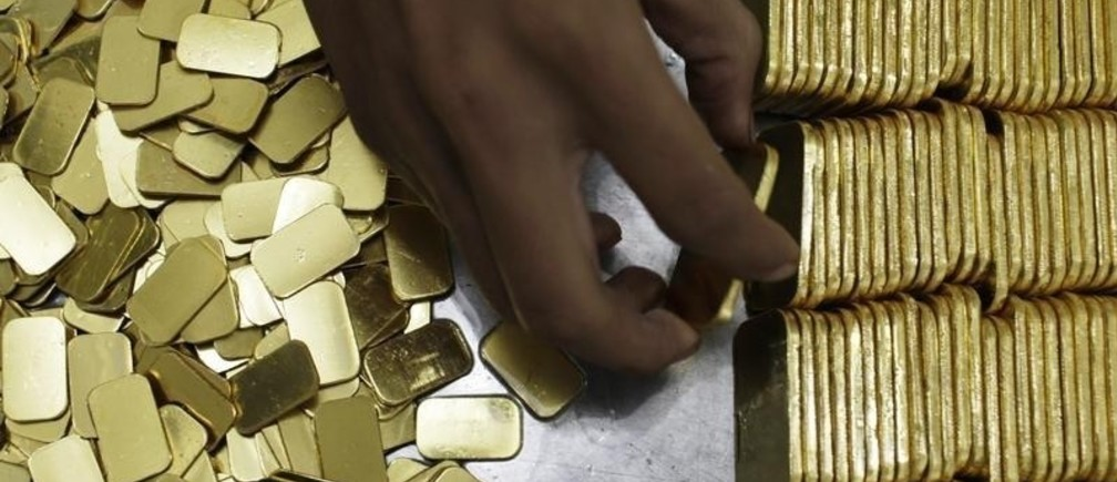An employee holds a gold piece, each weighing 100 grams, at the state-owned mining company PT Antam Tbk metal refinery in Jakarta July 13, 2012. Gold edged up on Monday, extending its winning streak into a seventh session as dimming prospects for global growth support expectations of more stimulus measures from central banks around the world. Picture taken July 13, 2012.