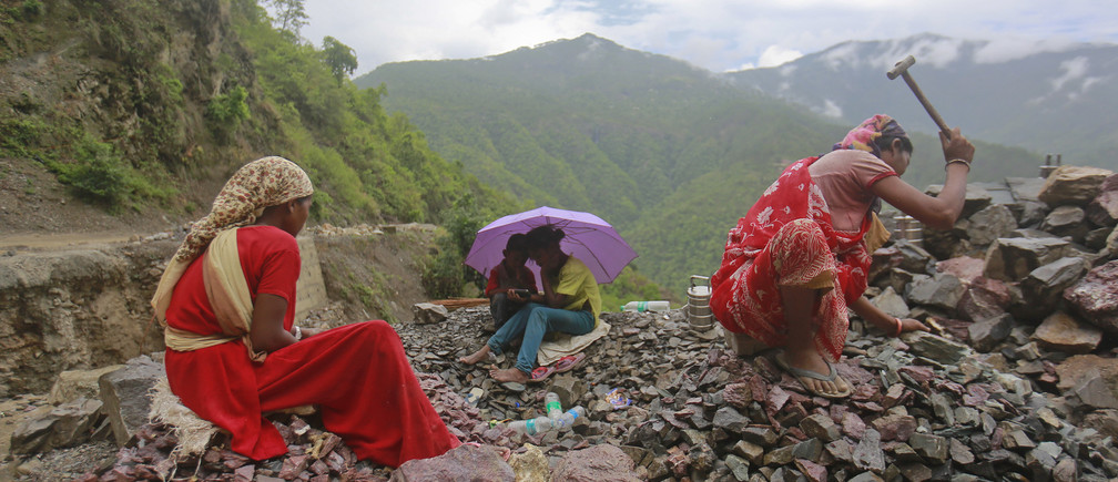 Workers repair a road damaged by a landslide, which was caused by heavy rainfall, as their children listen to songs on a mobile phone in Chamba, in the Himalayan state of Uttarakhand June 26, 2013.
