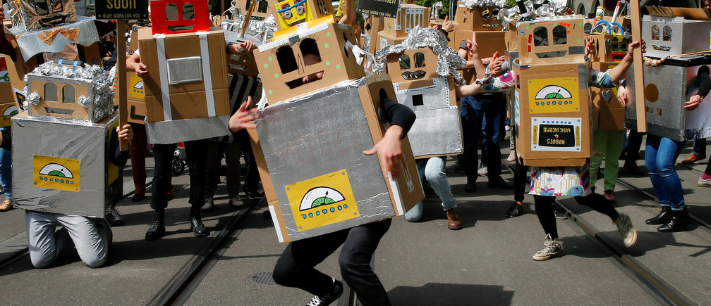 Protesters dressed as robots demand a basic income for everyone during a demonstration at the Bahnhofstrasse in Zurich, Switzerland April 30, 2016. REUTERS/Arnd Wiegmann - RTX2C8PX