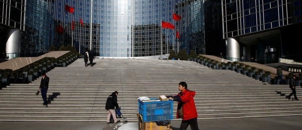 A delivery worker pushes a trolley loaded with parcels past the Grand Hyatt hotel in Beijing, December 4, 2018.  REUTERS/Thomas Peter - RC12D203E640