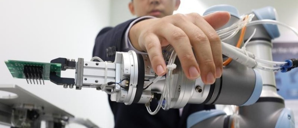 A Universal Robots employee demonstrates how a model of their industrial robot arms works in Singapore March 3, 2017. Picture taken March 3, 2017. REUTERS/Edgar Su - RTS14950