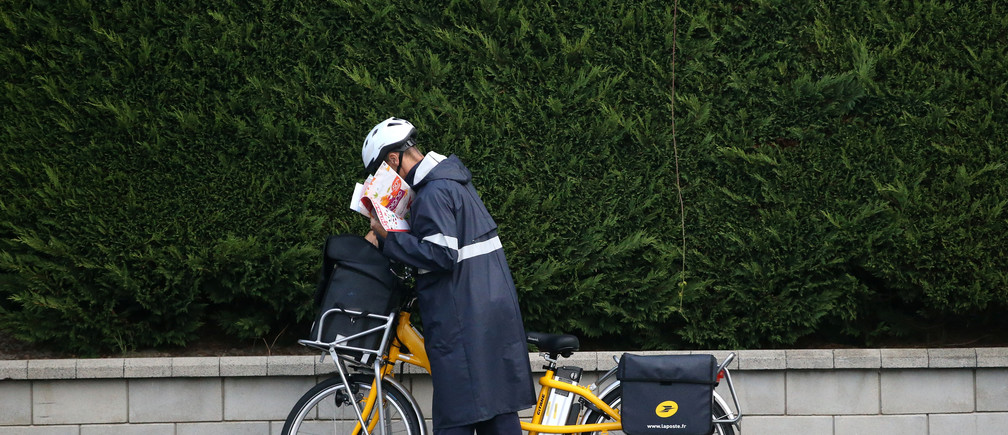 A postman of French postal service company La Poste distributes letters using an electrically-assisted bicycle in Vertou, France, September 1, 2017. REUTERS/Stephane Mahe - RC1D3F2A3F00
