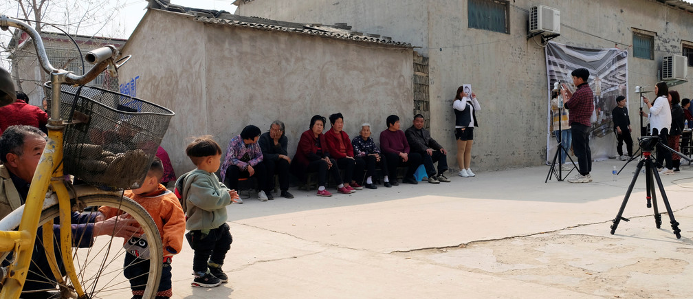 Workers from a Chinese data company take photos of the villagers for a facial recognition project.