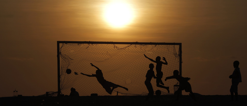 Angolan youths play soccer on a beach in the capital Luanda January 23, 2010.   REUTERS/Mike Hutchings
