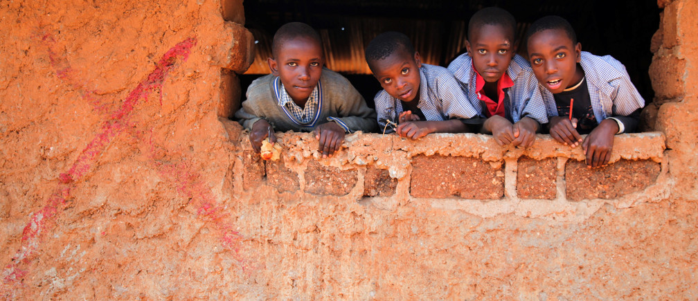 Children at Mashimoni School in Kibera peer through a classroom window of a building that was marked with a red cross in preparation for demolition in Nairobi, Kenya, September 23, 2016. Picture taken September 23, 2016. THOMSON REUTERS FOUNDATION/Katy Migiro     TPX IMAGES OF THE DAY - RTSRRMU