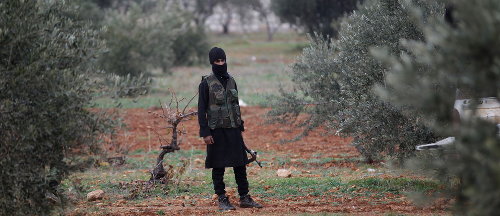 A member of al Qaeda's Nusra Front carries his weapon as he stands in an olive tree field, near villages which the Nusra Front said they have seized control of from Syrian rebel factions, in the southern countryside of Idlib, December 2, 2014. Picture taken December 2, 2014. REUTERS/Khalil Ashawi (SYRIA - Tags: CIVIL UNREST CONFLICT TPX IMAGES OF THE DAY) - GM1EAC31HVM01