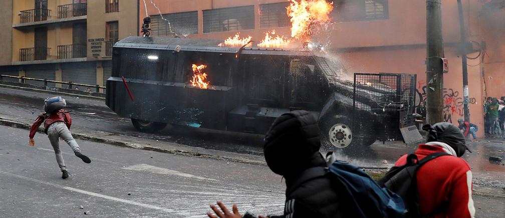 A police vehicle burns during a protest against Ecuador's President Lenin Moreno's austerity measures in Quito, Ecuador, 7 October 2019.