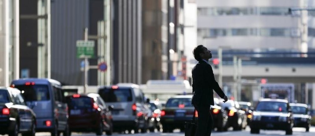 A businessman looks up as he crosses a street in a business district in central Tokyo, Japan, December 8, 2015. Japan's economy dodged recession in the third quarter with the initial estimate of a contraction revised to an annualised expansion of 1.0 percent, offering a glimmer of hope for policymakers struggling to end years of stagnation.  REUTERS/Thomas Peter - GF10000258269