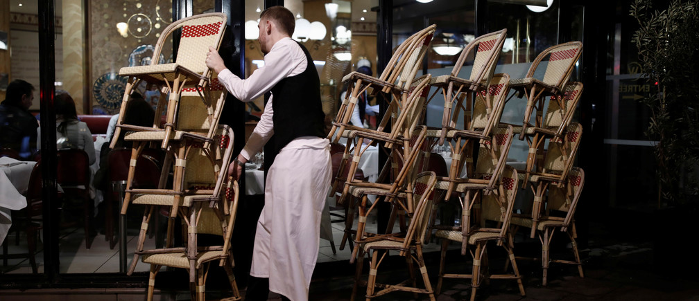 A restaurant employee clears out all the outside seats and prepares the closure of the place, as France's Prime Minister announced to close most all non-indispensable locations, notably cafes, restaurants, cinemas, nightclubs and shops from midnight on Saturday, March 14 due to concerns over the coronavirus (COVID-19), in Paris, France, early March 15, 2020. REUTERS/Benoit Tessier