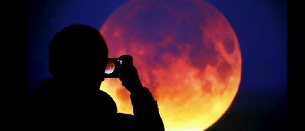 "A man takes picture of the screen displaying the moon, appearing in a dim red colour, which is covered by the Earth's shadow during a total lunar eclipse in Warsaw, Poland September 28, 2015. Sky-watchers around the world were treated when the shadow of Earth cast a reddish glow on the moon, the result of rare combination of an eclipse with the closest full moon of the year. The total ""supermoon"" lunar eclipse, also known as a ""blood moon"" is one that appears bigger and brighter than usual as it reaches the point in its orbit that is closest to Earth. REUTERS/Kacper Pempel"