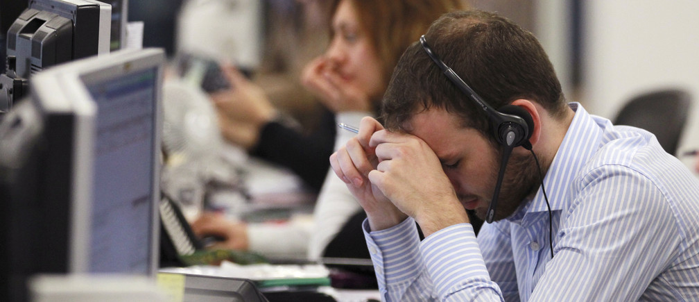 A worker on the IG Group's trading floor looks away from his screens in the City of London, October 4, 2011. Britain's top share index fell sharply by midday on Tuesday as worries over the euro zone debt crisis and the sustainability of global growth prompted investors to cut positions in riskier assets such as banks and commodity stocks. REUTERS/Olivia Harris (BRITAIN - Tags: BUSINESS POLITICS) - LM1E7A415WN01