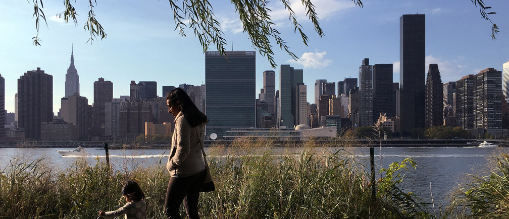 A woman and child walk at the Gantry Plaza State Park in the Queens borough of New York with midtown Manhattan including the Empire State Building (L) and the United Nations Headquarters (C) in New York, U.S. October 16, 2016.