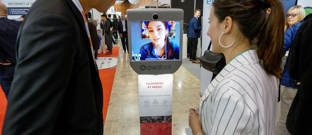 Visitors look at a Beam mobile telepresence robot by Awabot at the SIdO, the Connected Business trade show, in Lyon, France, April 6, 2017