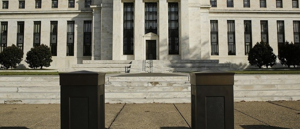 The United States Federal Reserve Board building is shown behind security barriers in Washington October 28, 2014. The U.S. Federal Reserve this week will likely reinforce its stated willingness to wait a long while before hiking interest rates after a volatile month in financial markets that saw some measure of inflation expectations drop worryingly low.     REUTERS/Gary Cameron    (UNITED STATES - Tags: BUSINESS POLITICS) - RTR4BX4X