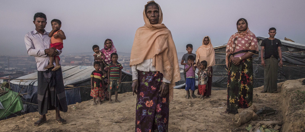 "I didn't think I would return here again, I hoped I would live in my homeland.""Rohingya grandmother Rahima Khatun (centre), 55, stands outside her shelter in Kutupalong camp, Bangladesh with her five children and seven grandchildren. Rahima was first made a refugee in 1978 at the age of 14, then again in 1992. On that occasion, her eldest daughter died of illness after the young family fled Myanmar. ; More than 640,000 Rohingya fled Myanmar, seeking safety in Bangladesh in 2017. While UNHCR intensified efforts to respond to this mass displacement and provide shelter in and around existing camps near Cox's Bazar, the sheer numbers mean there is much hardship to contend with. Whole families, young widowed mothers and unaccompanied minors were among those fleeing from persecution and violence in northern Rakhine state. Many arrived traumatised, in poor physical condition and in need of life-saving support. Cramped and deprived living conditions in the camps present concerns, but despite the hardships, the Rohingya feel safe compared to the situation back home. UNHCR is providing protection, food, clean water, shelter, health care, trauma counselling and reunification for separated families."