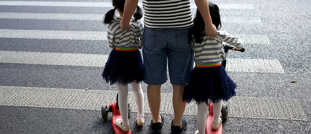 A father crosses a road with his twin daughters in Shanghai, China September 28, 2018.