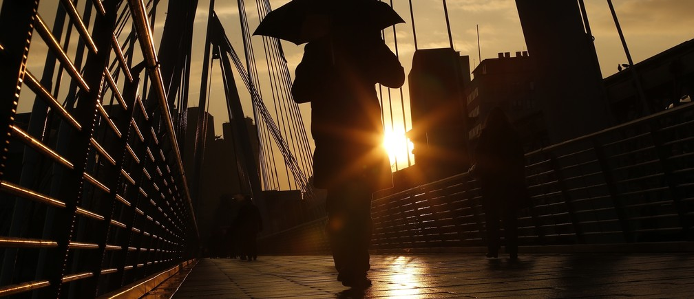 A pedestrian carries an umbrella as he walks over one of the Golden Jubilee Bridges in London January 31, 2014.