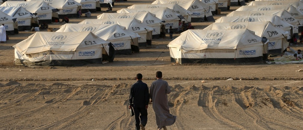 Iraqi refugees, who fled from the violence in Mosul, walk inside the Khazer refugee camp on the outskirts of Arbil, in Iraq's Kurdistan region, June 27, 2014.