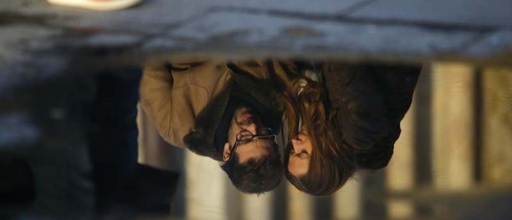 A couple is reflected in a puddle as they embrace on Valentine's Day in Venice February 14, 2014.  REUTERS/Max Rossi (ITALY - Tags: SOCIETY) - GM1EA2F059S01