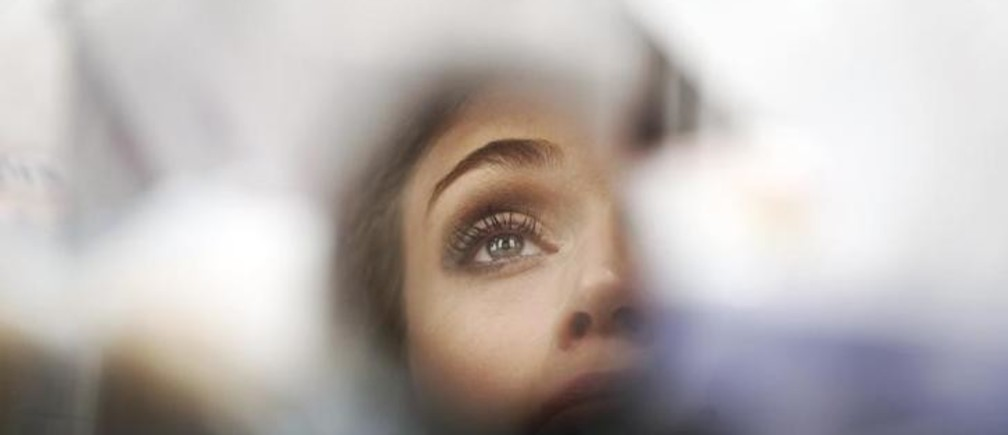 A model is reflected in a small mirror as she gets made up during Cibeles Madrid Fashion Week September 19, 2011. REUTERS/Susana Vera (SPAIN - Tags: FASHION)